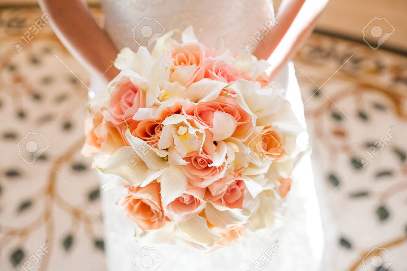 Bride with beautiful orange and pink wedding bouquet of flowers bride with beautiful orange and pink wedding bouquet of flowers consisting of white mini calla lilies mightylinksfo