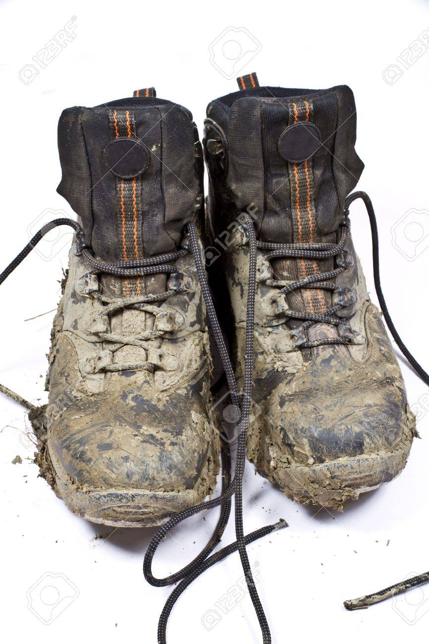 Pair of muddy , worn walking or hiking boots on a plain background Stock Photo - 6681642