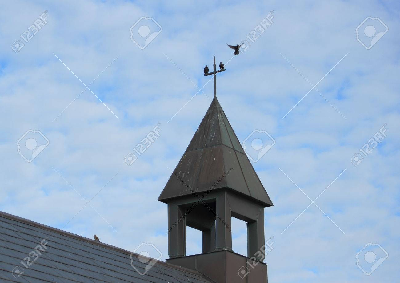 bell tower of small simple church with cross and birds stock photo
