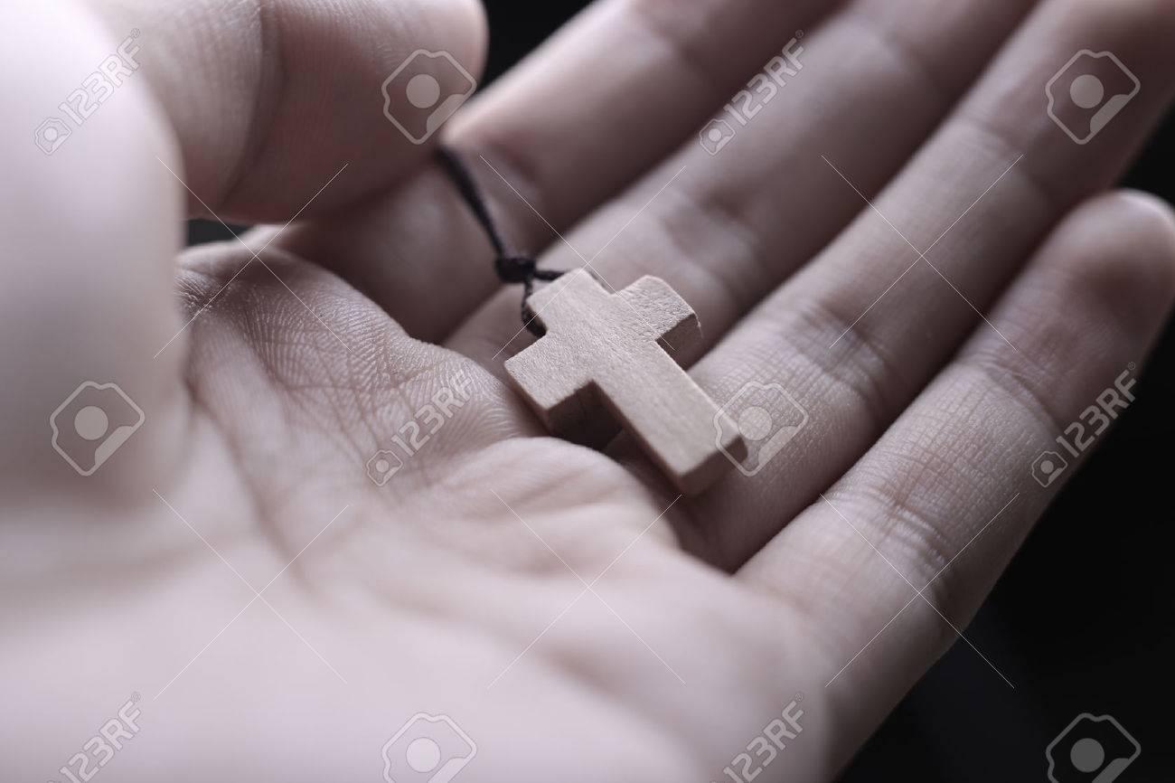 d10d4d579 Closeup of praying hand holding the wooden cross. Stock Photo - 46602392