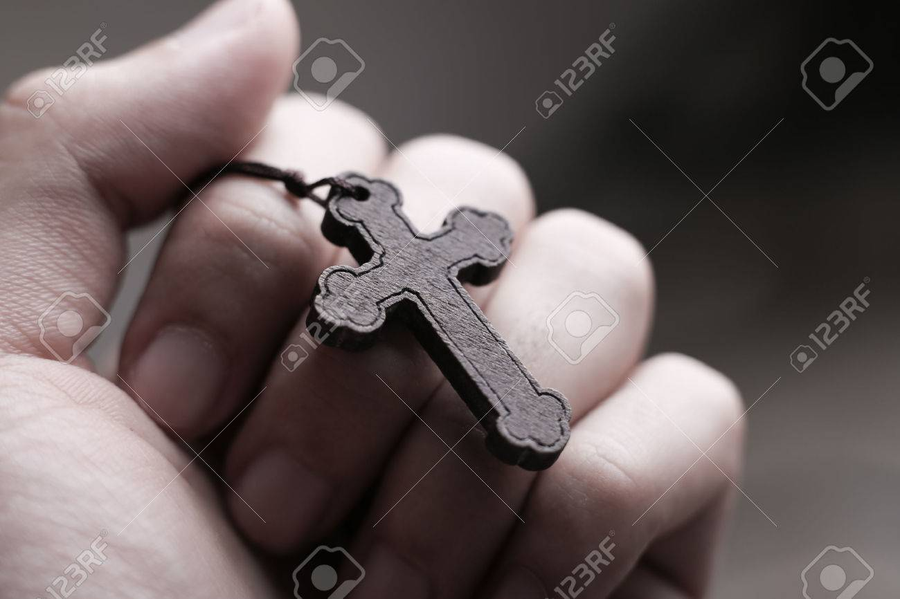 73a99e2f6 Closeup of praying hand holding the wooden cross. Stock Photo - 46602396