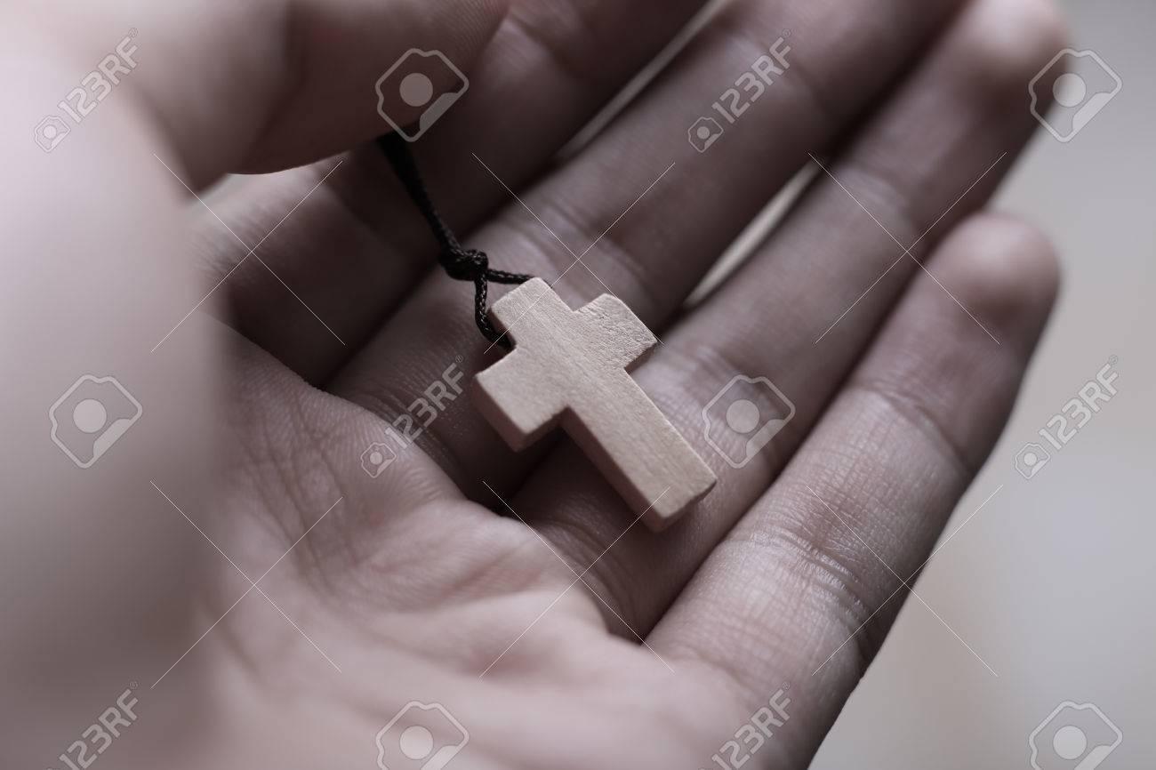 f1b85b22e Closeup of praying hand holding the wooden cross. Stock Photo - 46602445