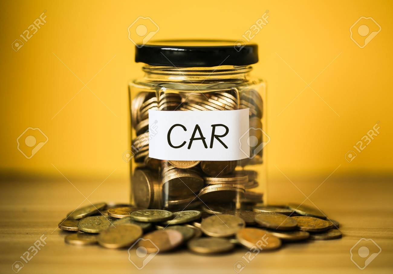 A lot coins in glass money jar with yellow background. Saving for car concept. - 98012334