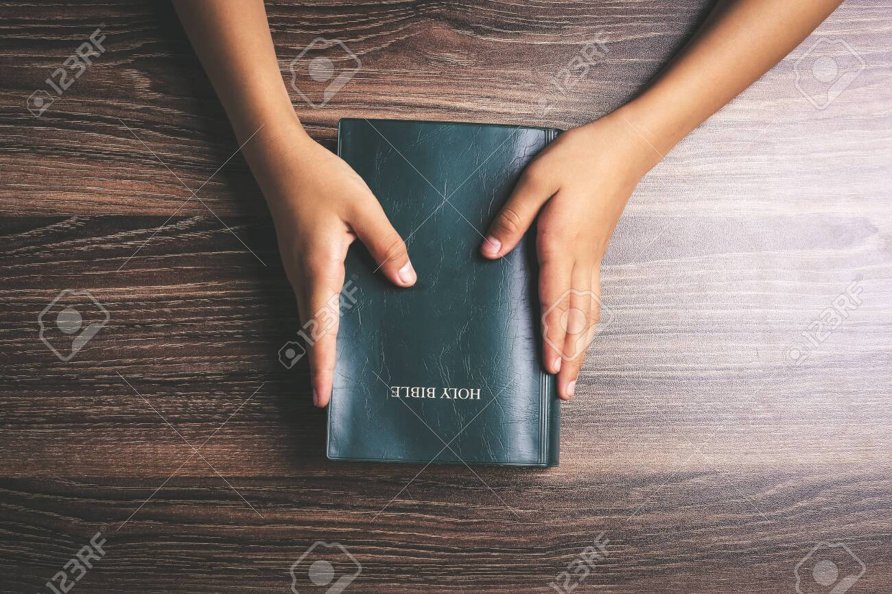 Hands with holy bible on the wooden desk. - 124032431