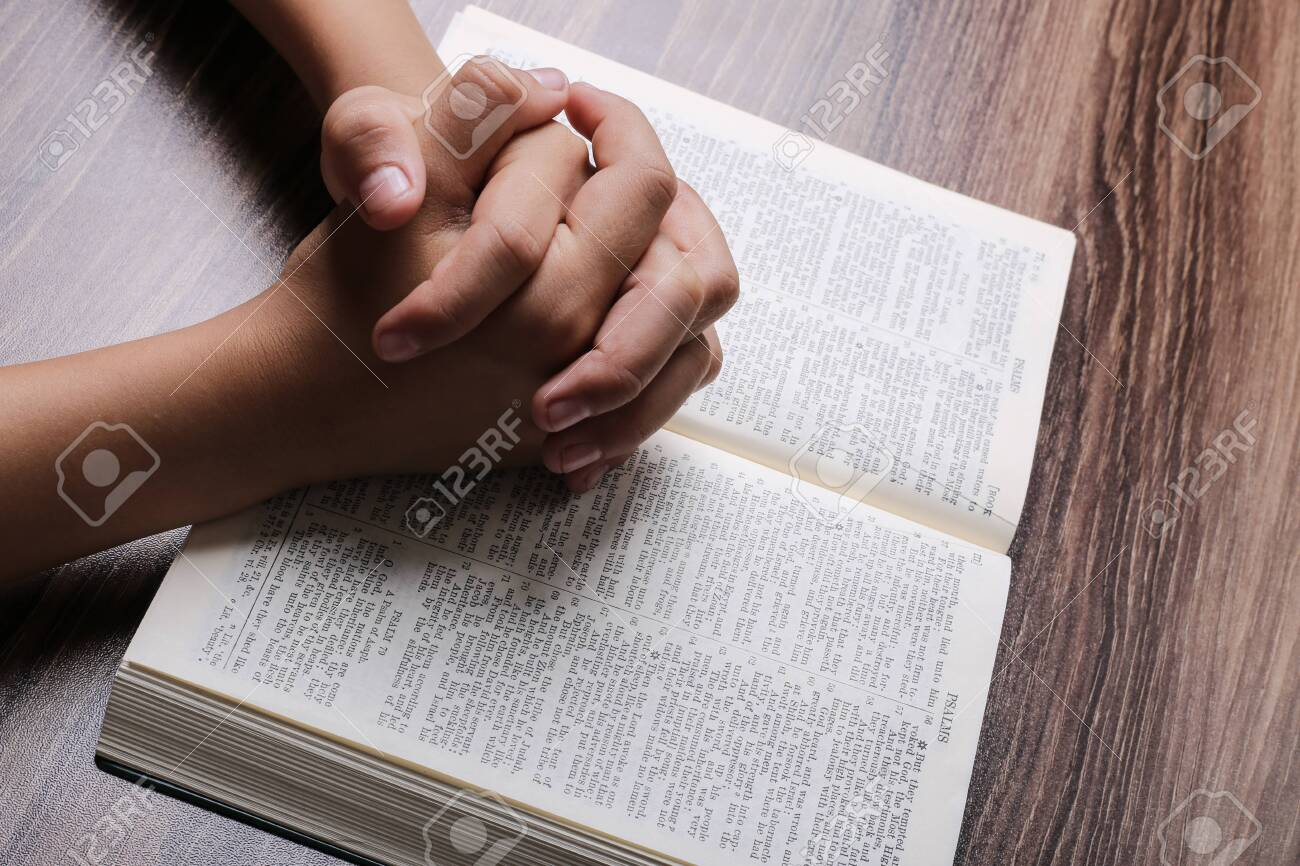 Praying hands with opened holy bible on the wooden desk. - 124032432