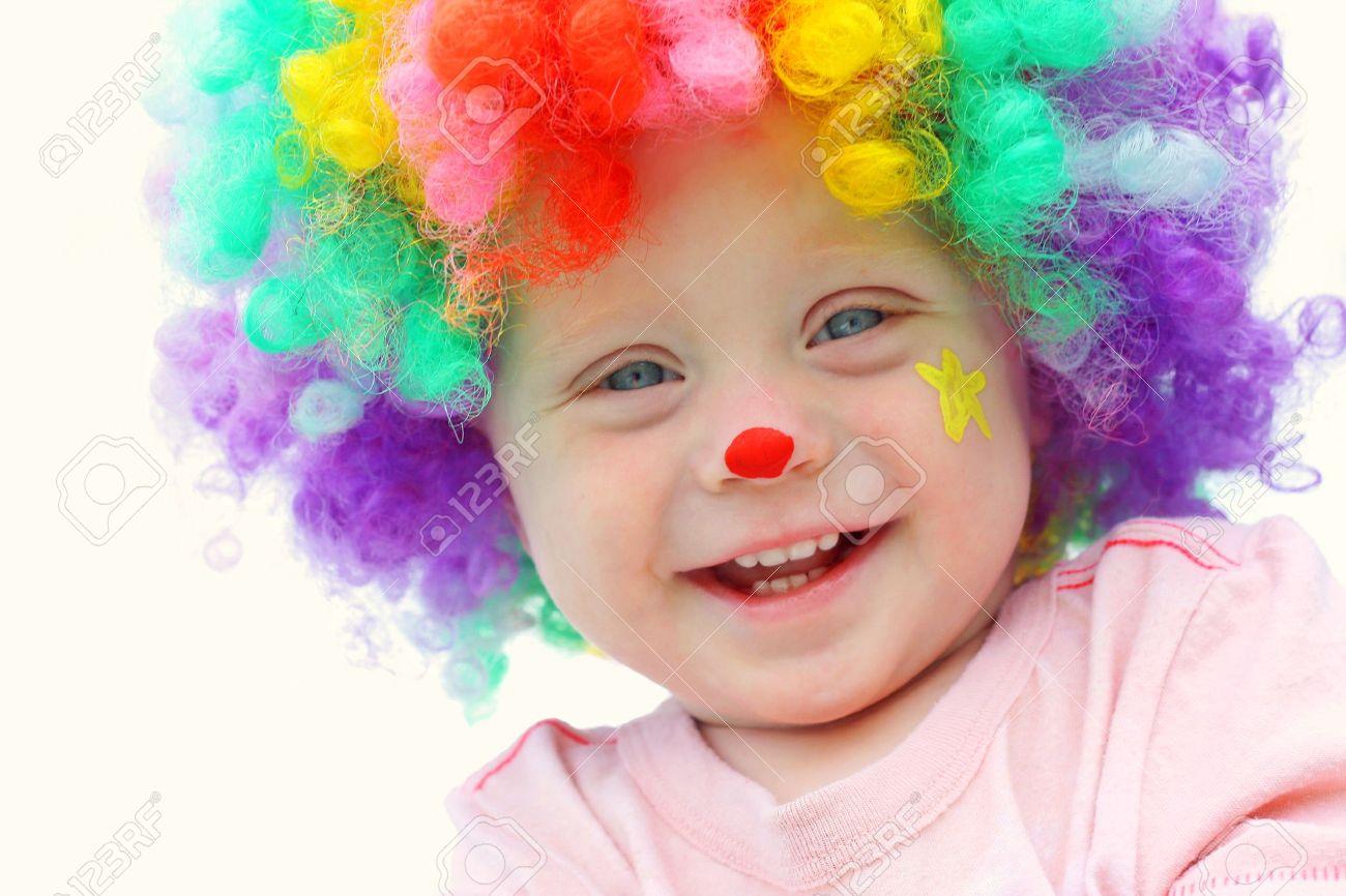 Banque dimages , Un mignon, petit garçon souriant est habillé dans une perruque de clown avec le clown maquillage peinture de visage