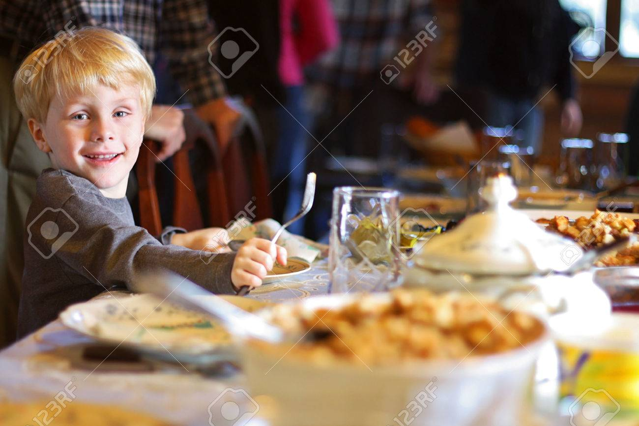 a happy young child is smiling as he sits at the holiday dinner table with a fork and plate, waiting for his meal - 24265151