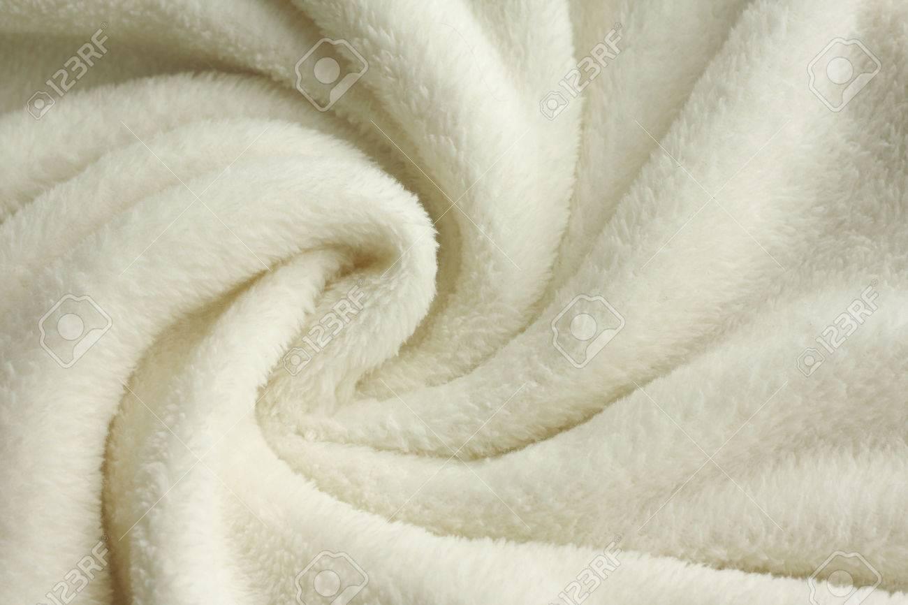 a warm, white, plush micro fleece blanket is swirled into a cirular pattern background - 26105629