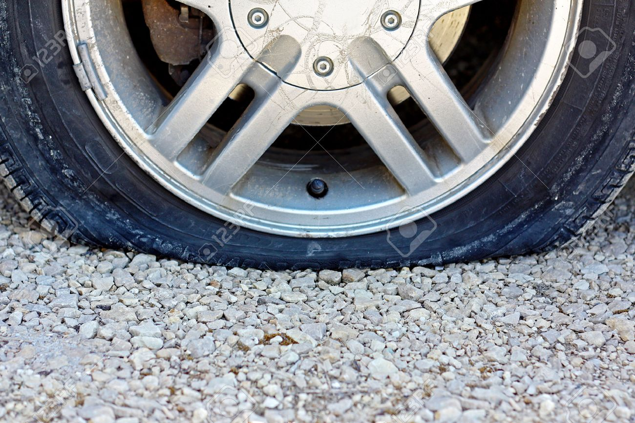 a close up, centered view of a flat car tire that has popped on a gravel road. Room for copy-space. - 27537761
