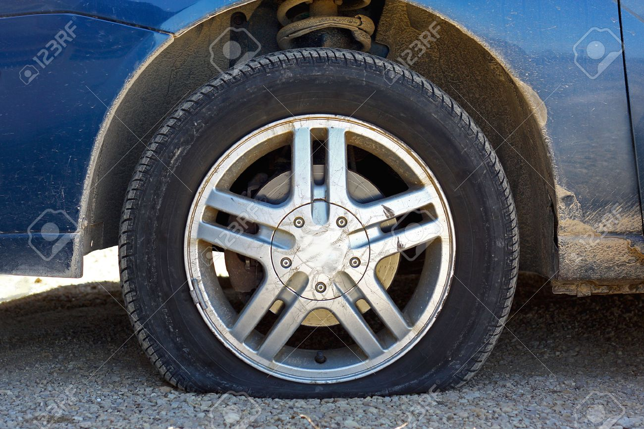 flat tire. Unique Flat Close Up Of A Flat Tire Blue Car Centered On Gravel Road Stock Photo Inside Flat Tire