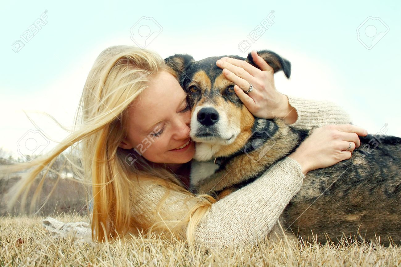 a young caucasian woman is laying outside with her German Shepherd Dog, hugging him lovingly - 27613758