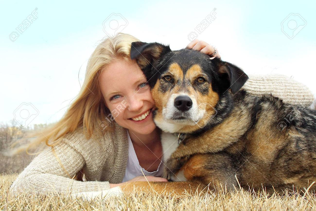 a happy young woman and her German Shepherd dog are laying on the grass outside hugging - 27592628