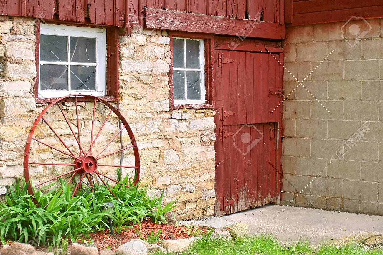 An Antique Metal Wagon Wheel Is Leaning Up Against An Old Stone ...
