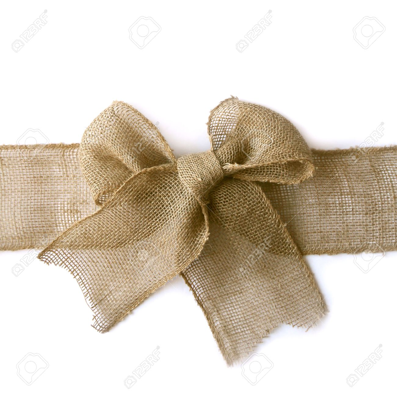 A natural colored burlap wribbon is tied in a bow as if wrapped around a Christmas present, isolated on a white background, with vertical copyspace - 34104268