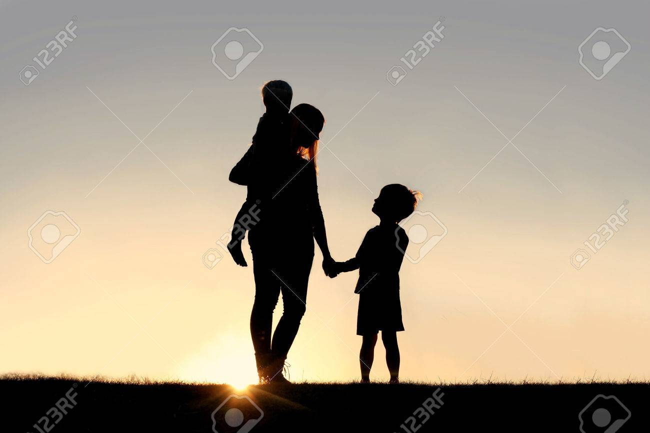 Silhouette of a young mother lovingly holding hands with her happy little child, while holding his baby brother, outside in front of a sunset in the sky. - 38380654