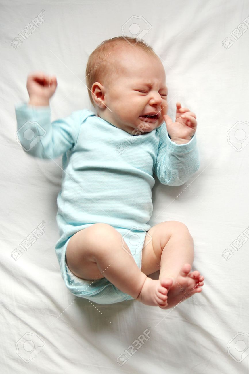 A cute one month old newborn baby is laying on her back in the crib, crying. - 38707821