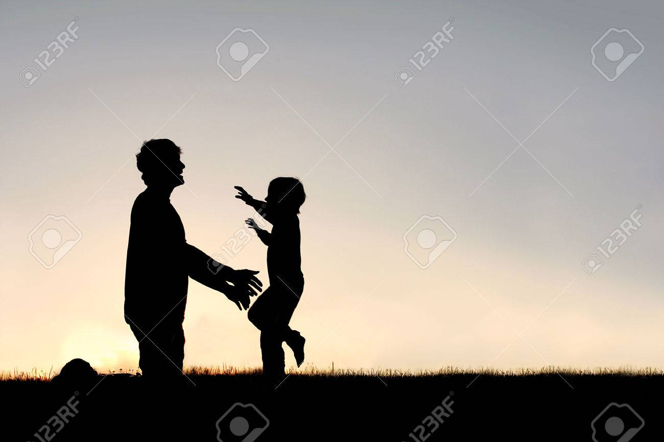 Silhouette of a happy young child smiling as he runs to greet his father with a hug at sunset on a summer day. - 40730026