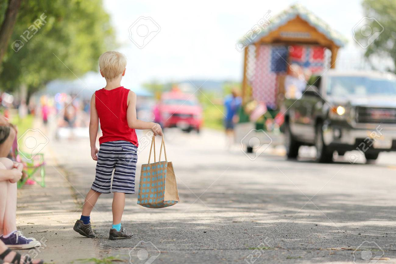 A young boy child standing outside in the summer watching a small town american parade and holding a candy bag. - 43762914