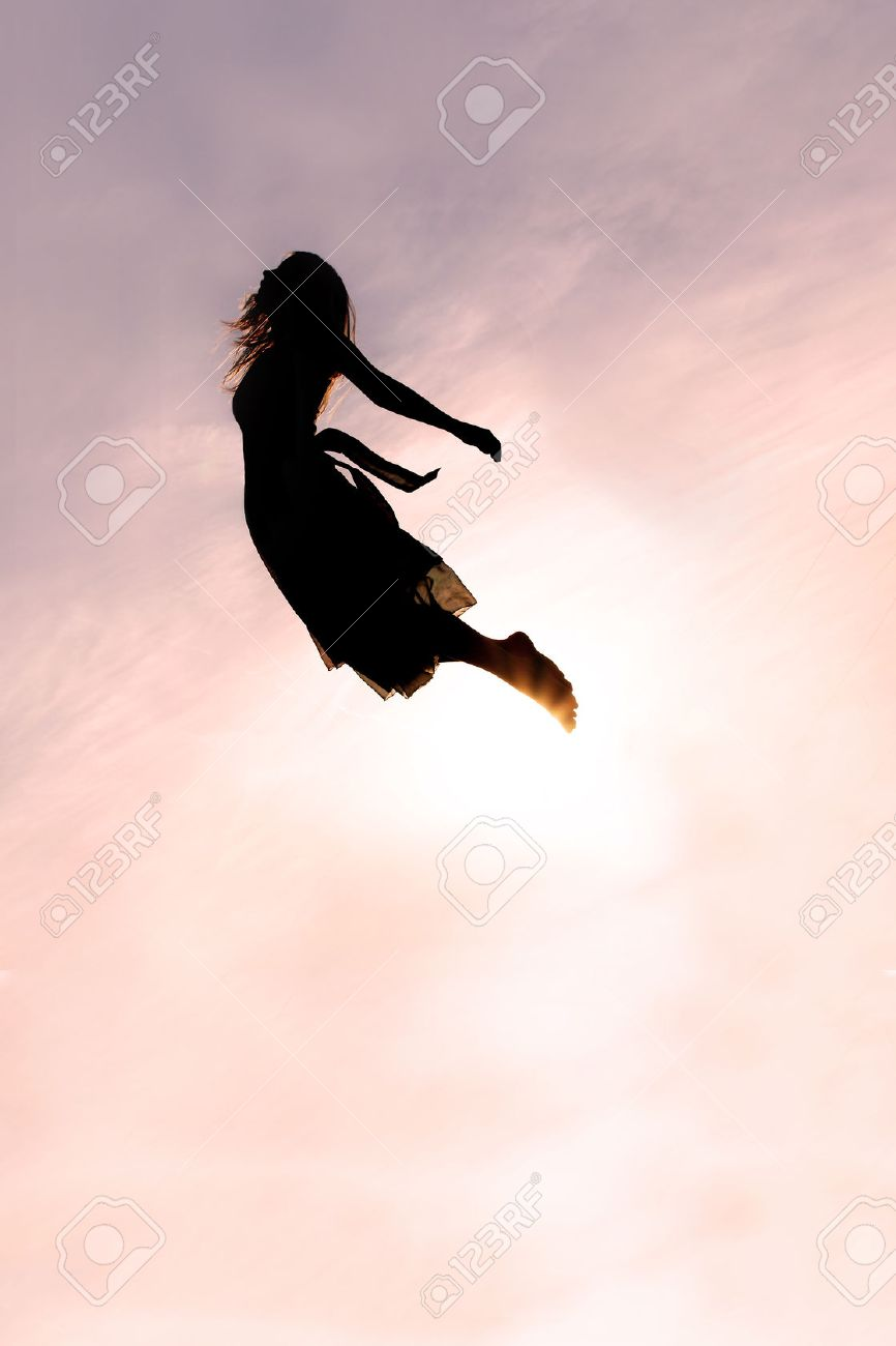 Silhouette of a young woman falling head-first through the sky at sunset. - 44953772