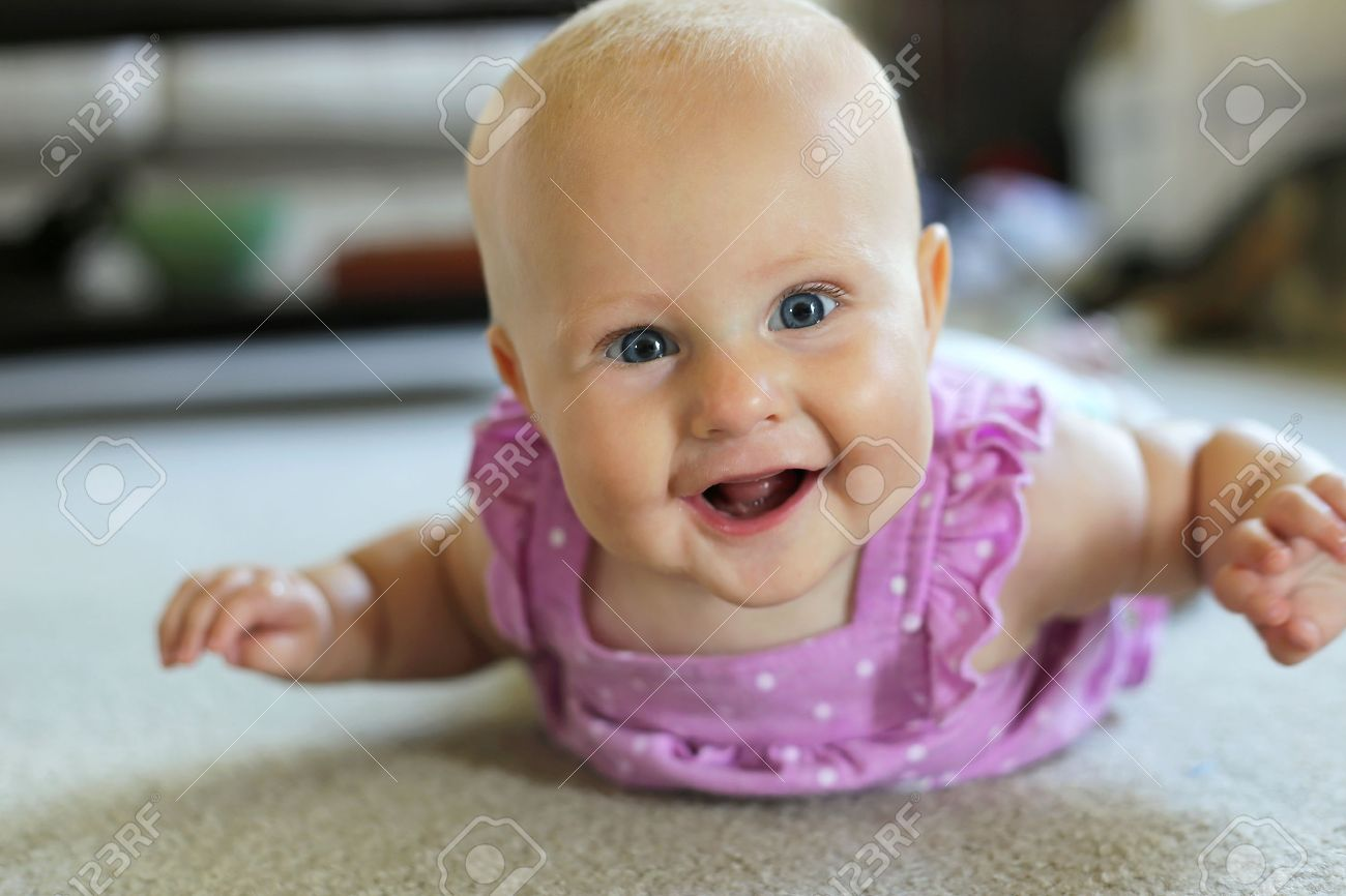 A happy 6 month old baby girl is laying on her tummy at home smiling and trying to crawl. - 45092532
