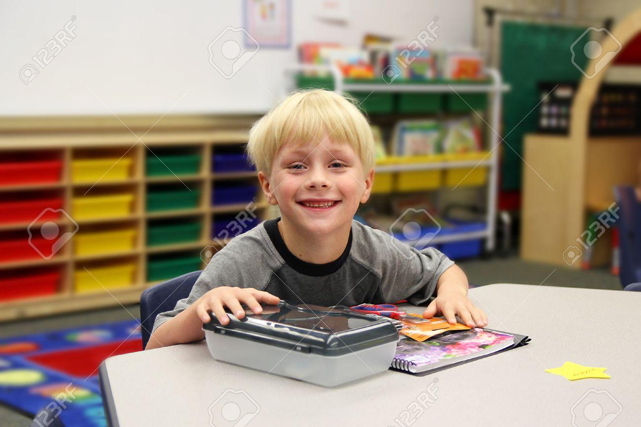 Un jeune garçon est assis à son bureau sur son premier jour d