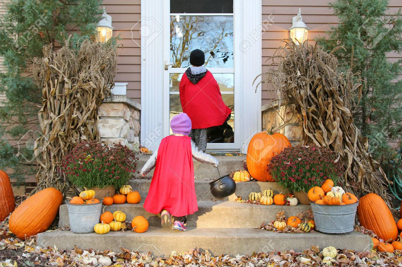 Two young children dressed up in costumes are waiting at a house for candy while Trick-or-Treating on Halloween. - 45092551