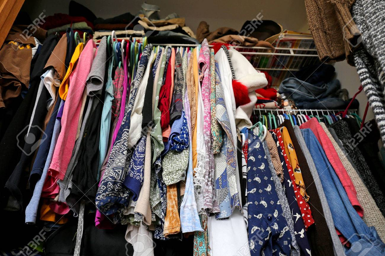 A Messy Young Womenu0027s Closet Is Fill With Many Outfits Of Colorful  Clothing, Shirts,