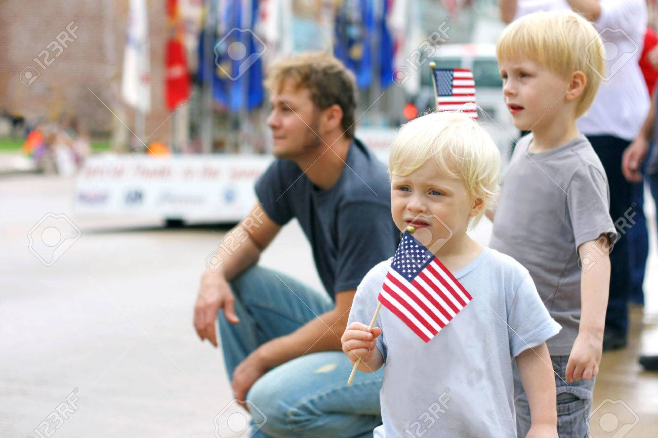 Two young boy children are waving American Flags as they stand with their Father at watch a Patriotic Parade Event in the United States. - 65013928