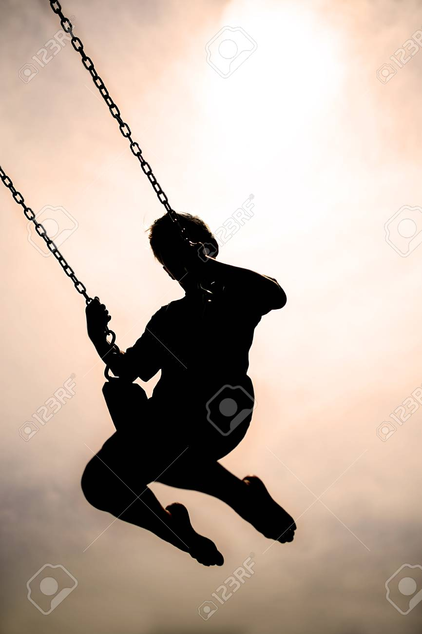 A Black Silhouette Of A Little Child Swinging On A Swingset At