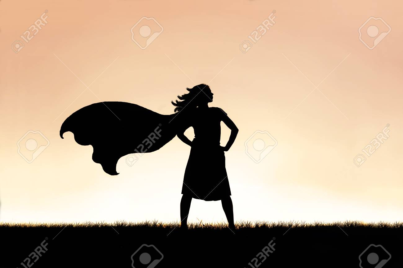 The silhouette of a strong, beautiful caped super hero woman stands isolated against a sunset in the sky background. - 106119736