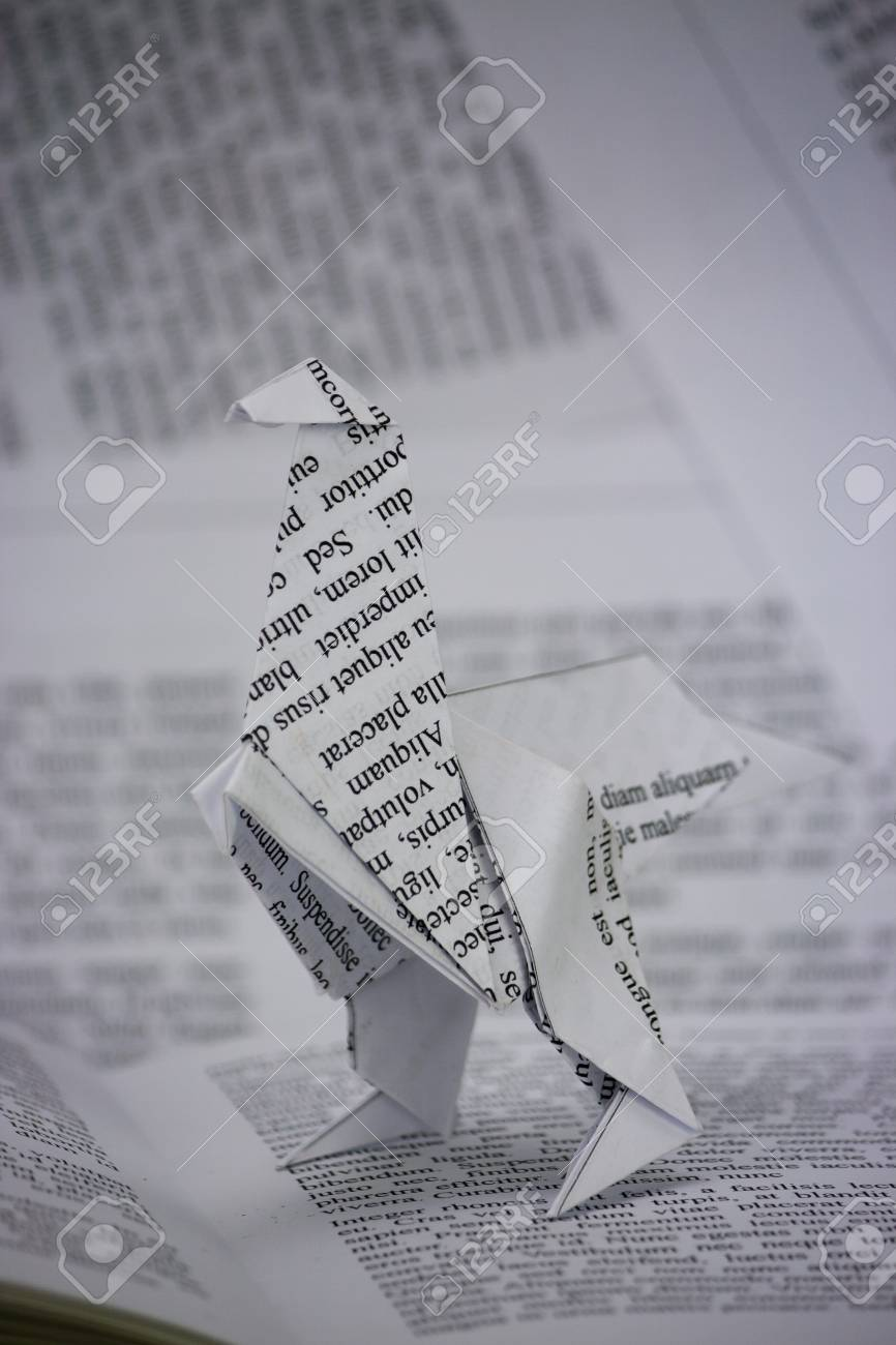 Origami Dinosaur With Words Coming Out Of A Book Stock Photo