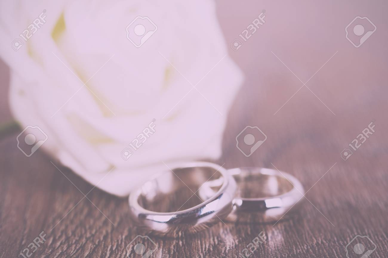 Pair Of White Gold Wedding Rings On A Wooden Background Vintage ...