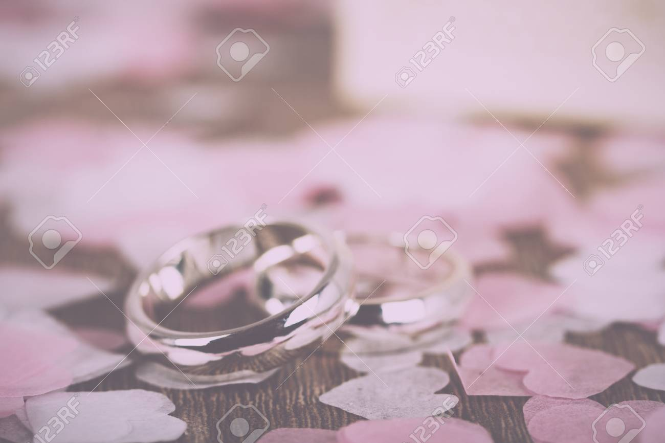 Pair Of White Gold Wedding Rings On A Wooden Background With.. Stock ...