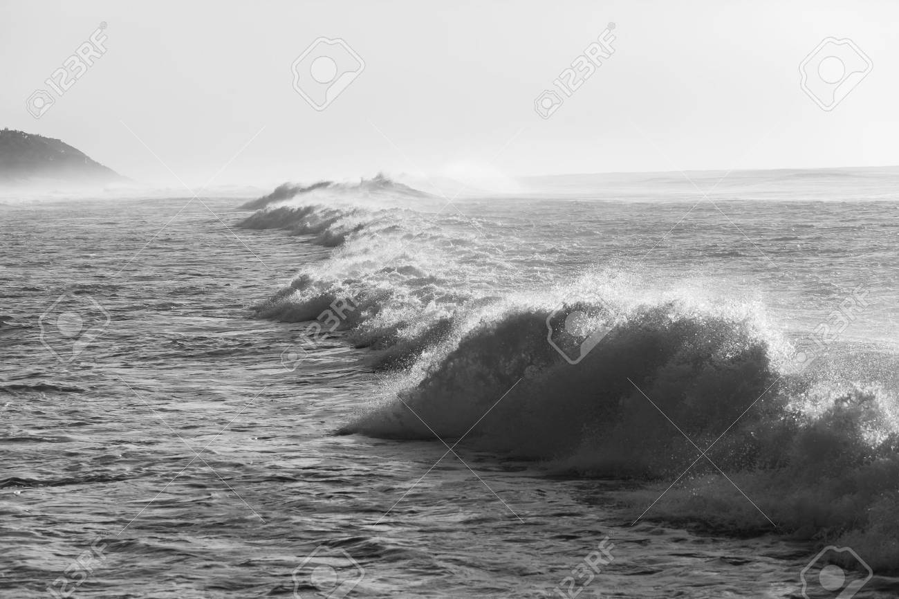 Ocean waves crashing water power in black and white along beach coastline stock photo 40296004