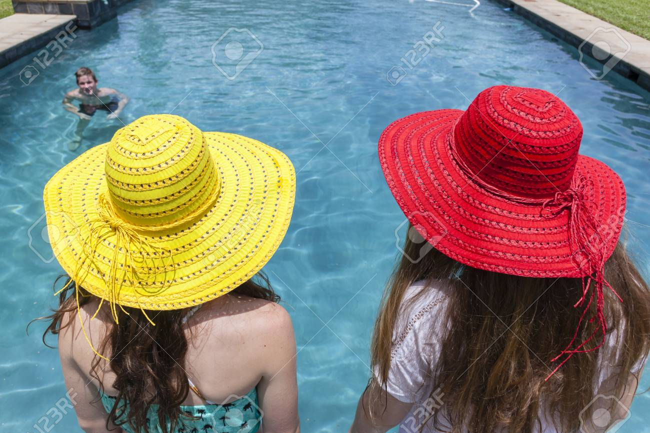 Stock Photo - Teenagers girls red yellow hats summer boy swimming pool  recreation 8f721cee8ec