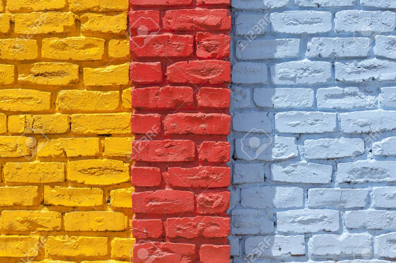 brick wall painted yellow red blue outside decor texture detail color closeup background stock photo