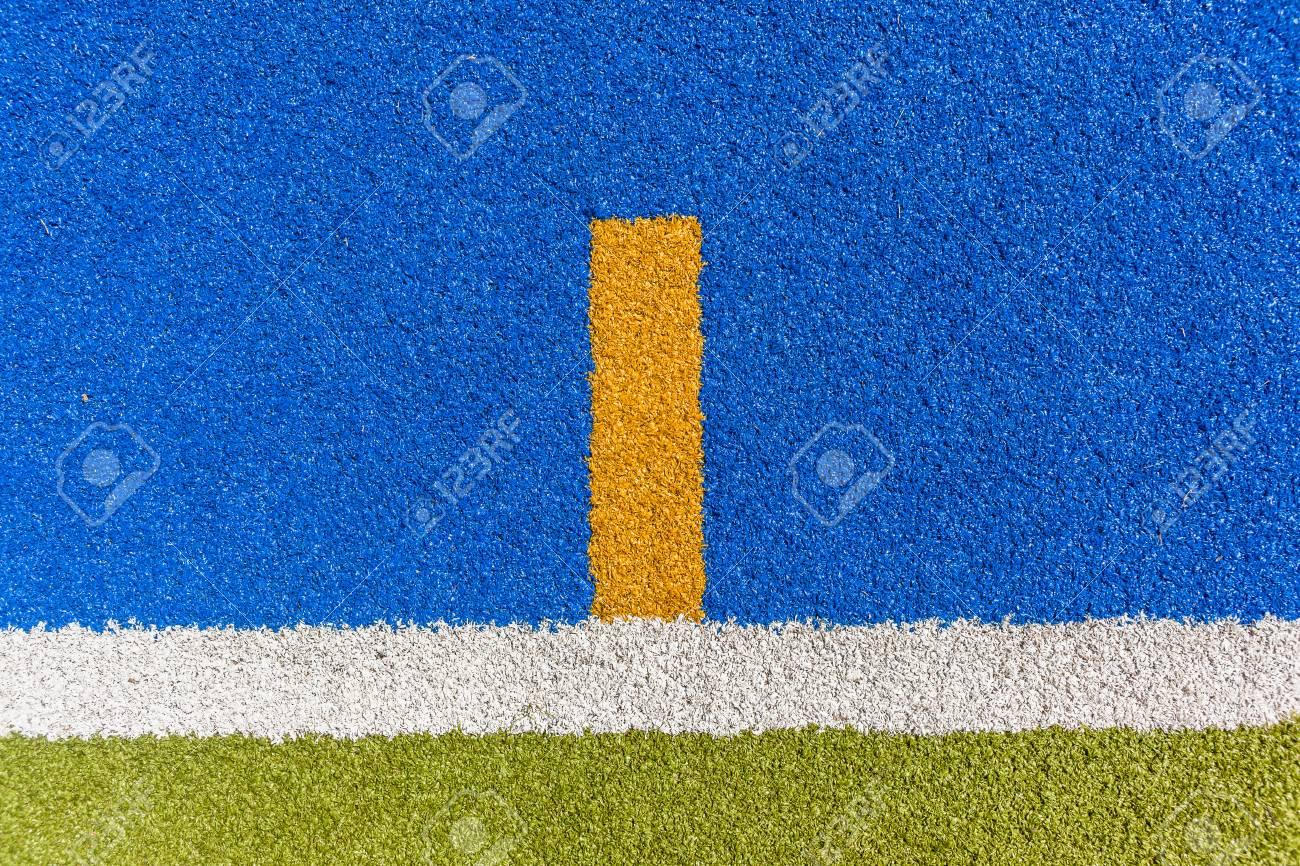 Se divierte la línea blanca del límite del primer del campo del césped  artificial del astro con el detalle verde y azul.