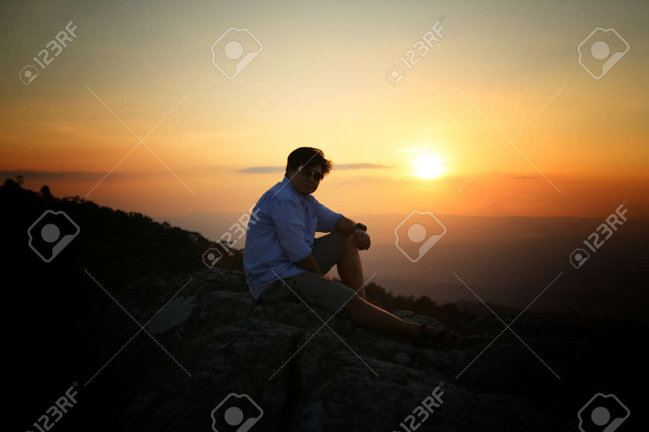 a man on a mountain top. Person on the rock. Sport and active life concept. Beauty world. - 159905131