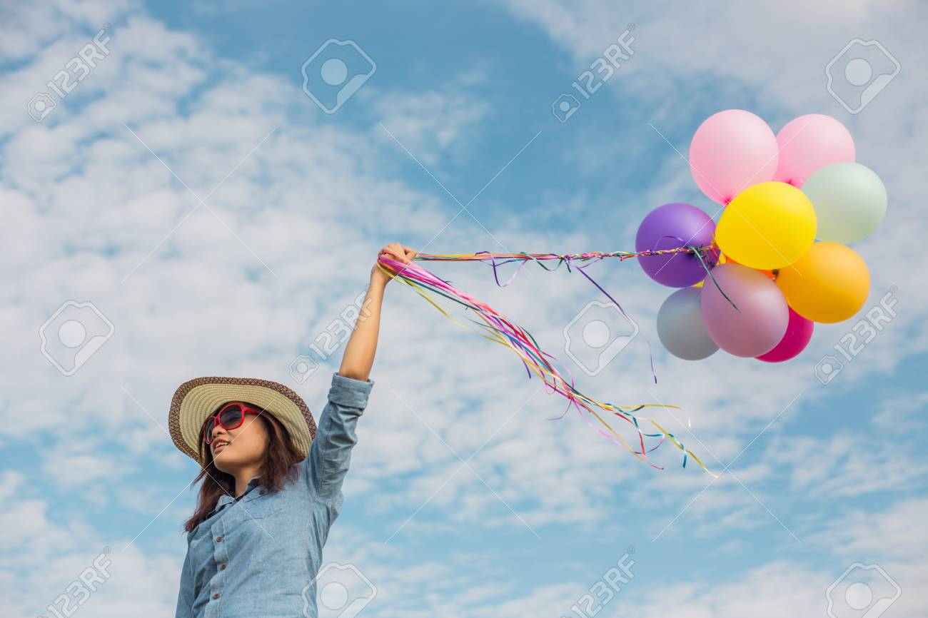 Beautiful girl jumping with balloons on the beach stock photo 73597140