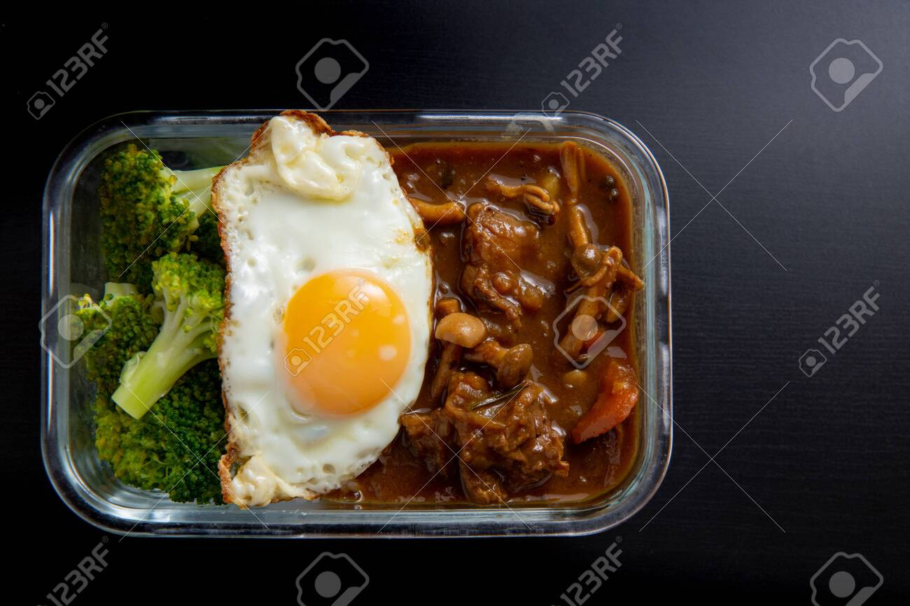 Beef curry rice in glass lunch box on black wooden dining table ( Onsen tamago, Potato, enoki mushroom, onion, broccoli, Japanese style) - 135771074
