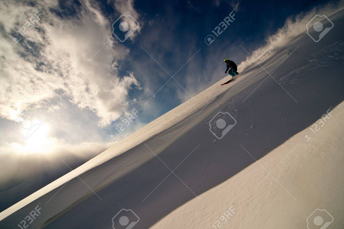 Freerider moving down a slope. Winter sunset in the mountains Stock Photo - 8914223