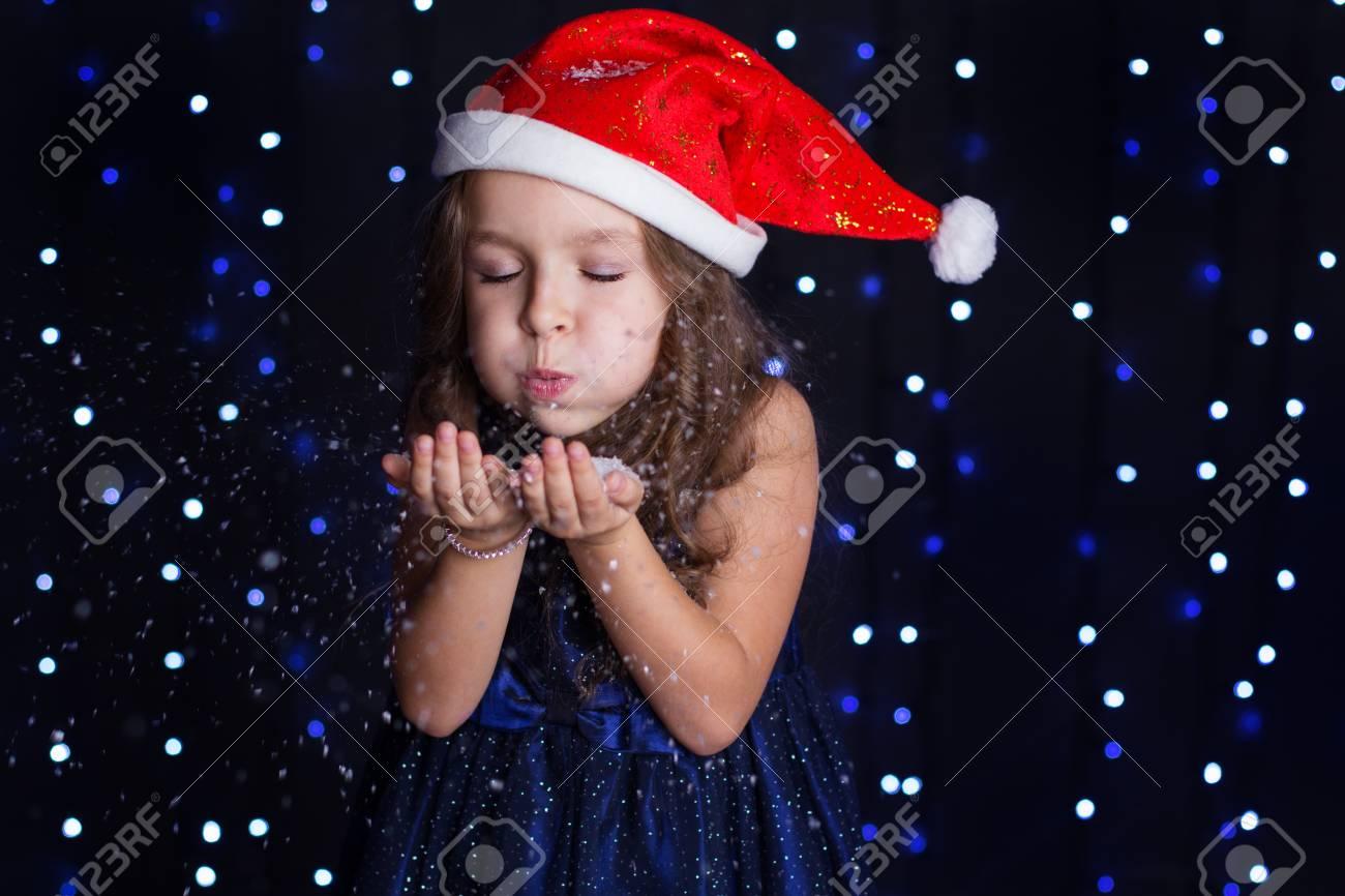 Foto de archivo - Una niña de niño pequeño está soplando copos de nieve  blancos en una escena de fondo del estudio con luces para un concepto de  vacaciones. 591ff4e348f
