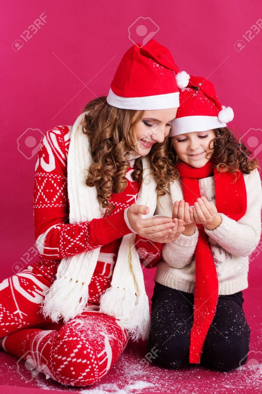 Foto de archivo - Pretty dos hermanas niñas están soplando nieve artificial  usando ropa de abrigo de invierno aislados sobre fondo rojo 7f7e4969148