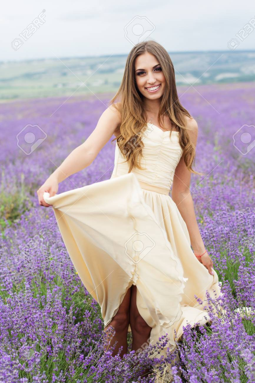 Young Woman Is Wearing Nice White Dress Walking At Field Of Purple