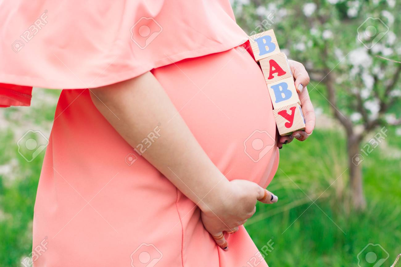 Pretty Pregnant Girl Is Holding Wooden Babies Bricks In Hands