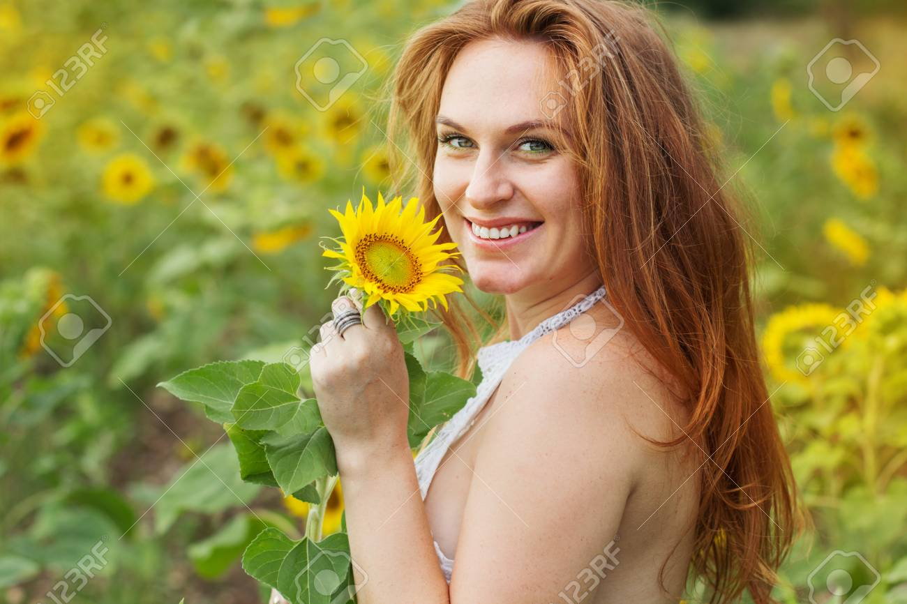 f819949ee24 Redheared happy smiling girl in field with yellow sunflowers Stock Photo -  60026684