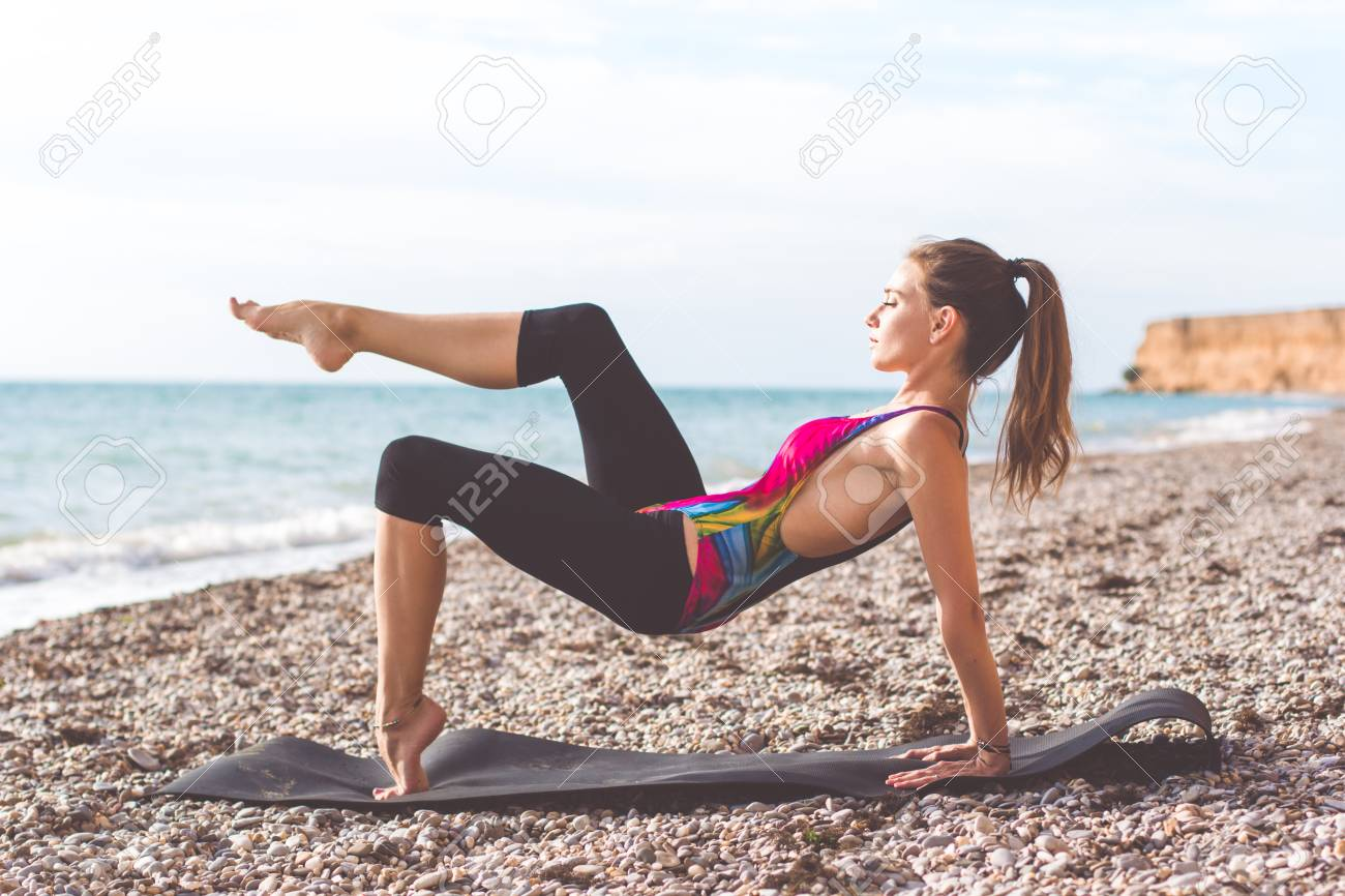 junge dünne schöne frau ist sportliche kleidung trägt auf der matte  stretching und yoga an der küste zu tun, sommerzeit
