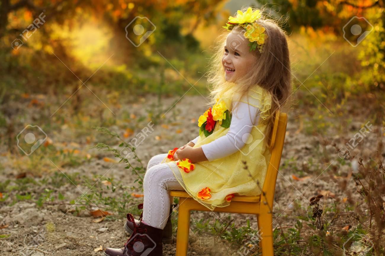 Little Girl Is Sitting On Yellow Chair In Autumn Garden Stock Photo ...