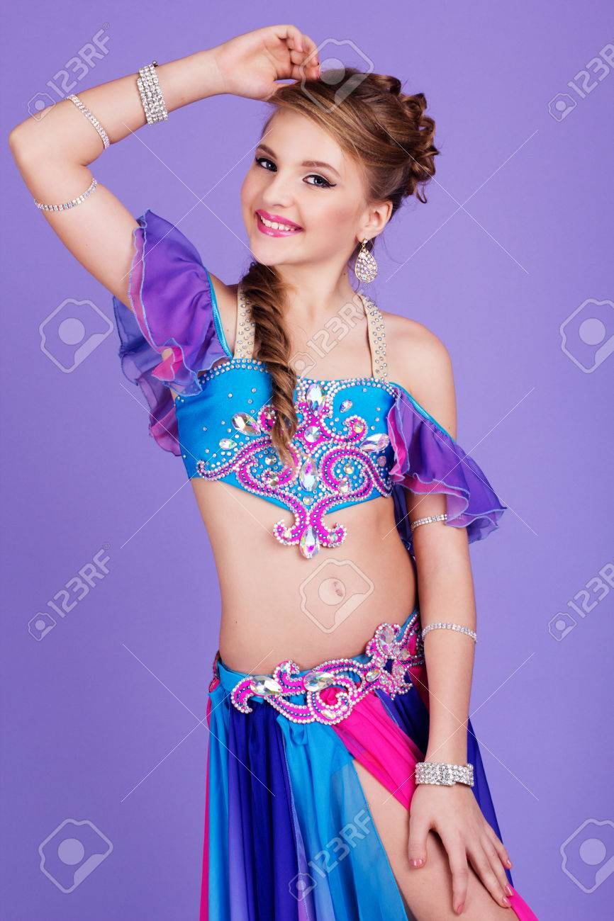 Beautiful belly dancer child girl is wearing a colorful fashion beautiful belly dancer child girl is wearing a colorful fashion costume isolated on purple stock baditri Image collections