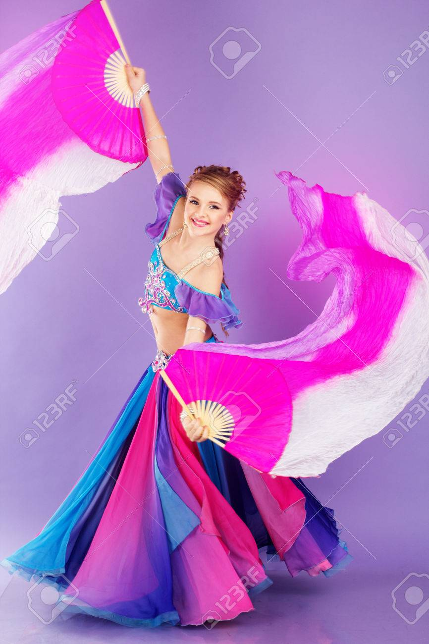 Beautiful belly dancer girl is wearing a colorful fashion costume beautiful belly dancer girl is wearing a colorful fashion costume and holding fan isolated on baditri Image collections
